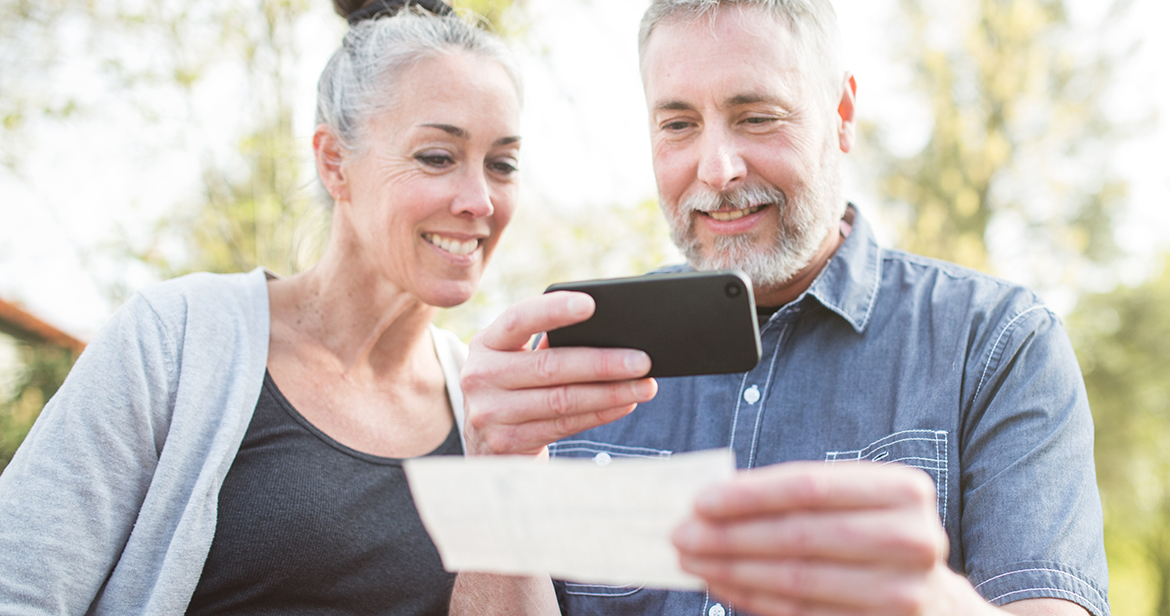 elderly couple using smartphone to take picture of check