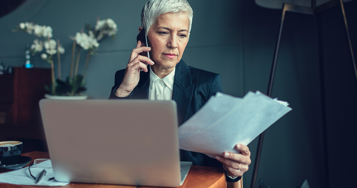 elderly woman in business attire on phone holding papers