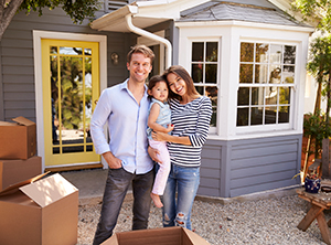small family standing in front of house with moving boxes around them