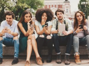 group of young adults with phones and tablets