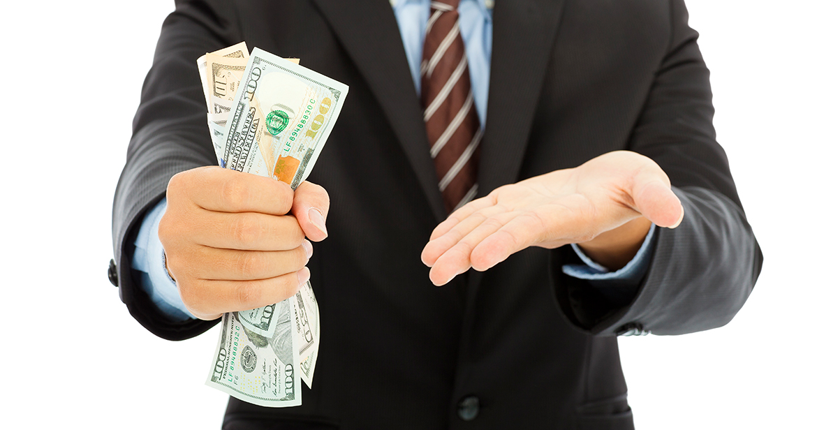 man holding cash in one hand and gesturing to it with the other hand