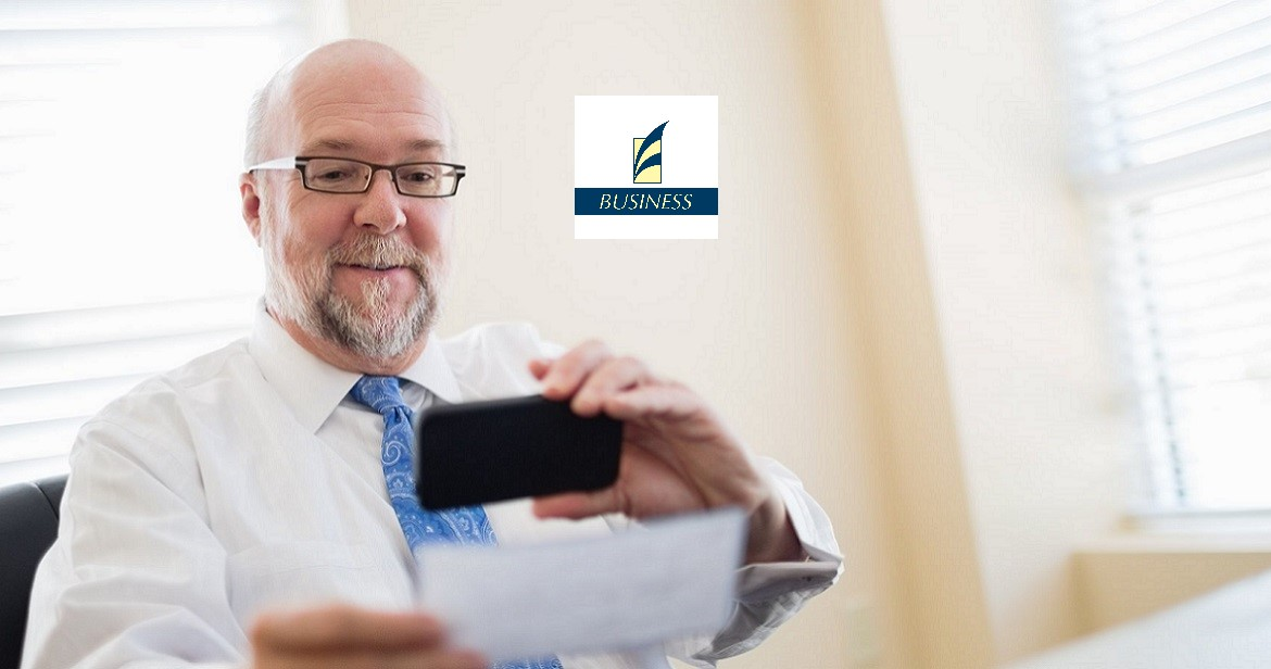 Businessman using business app to take picture of check for mobile deposit