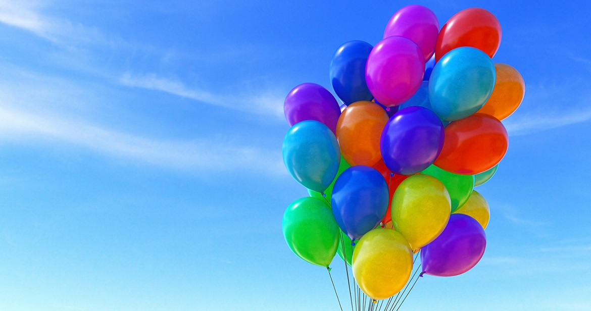 A group of colorful balloons tied together into a bunch, isolated on a soft blue sky background.
